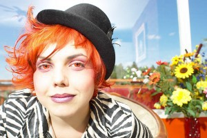 Woman with bright orange hair and a hat uid 1181384